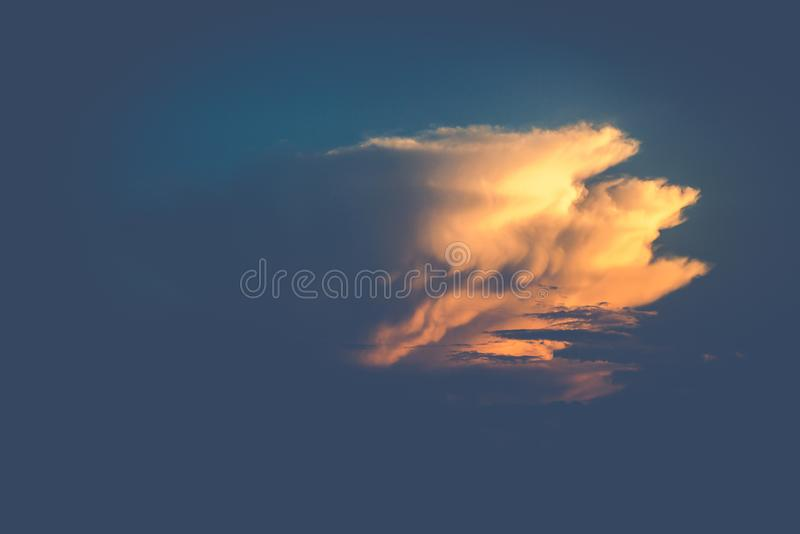 One yellow big cloud in blue sky royalty free stock image