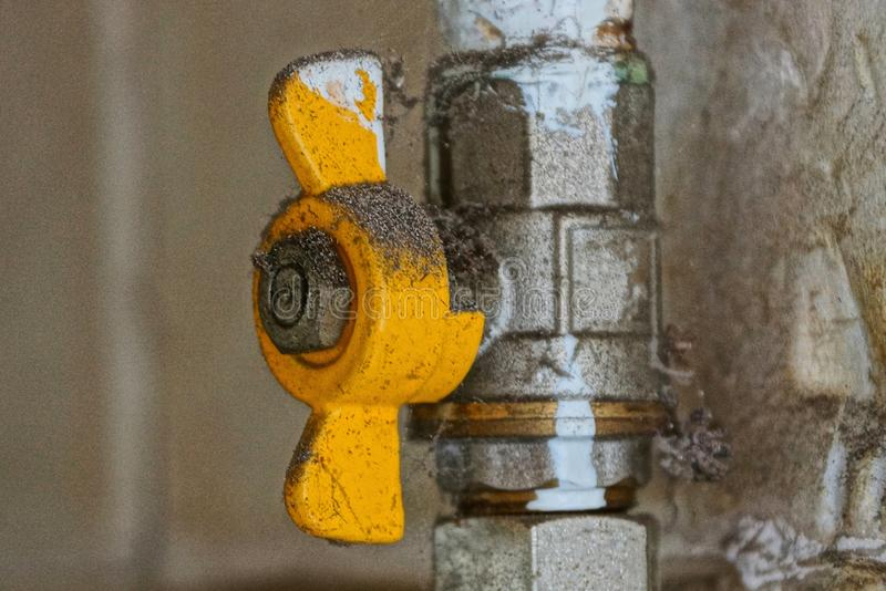 Yellow dirty faucet on a gray metal pipe stock images