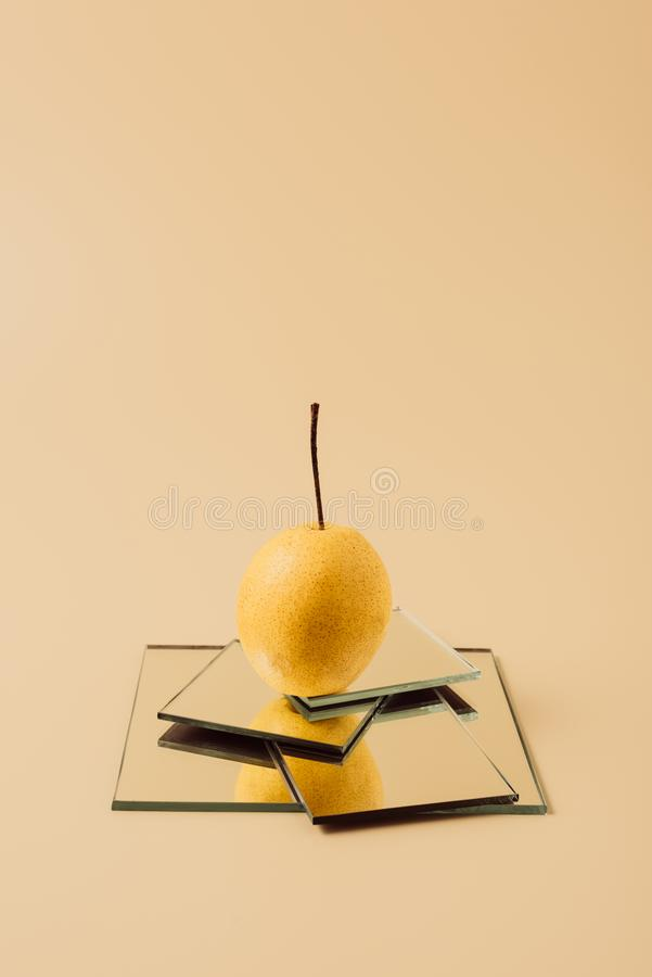 one yellow pear on mirrors on beige stock image
