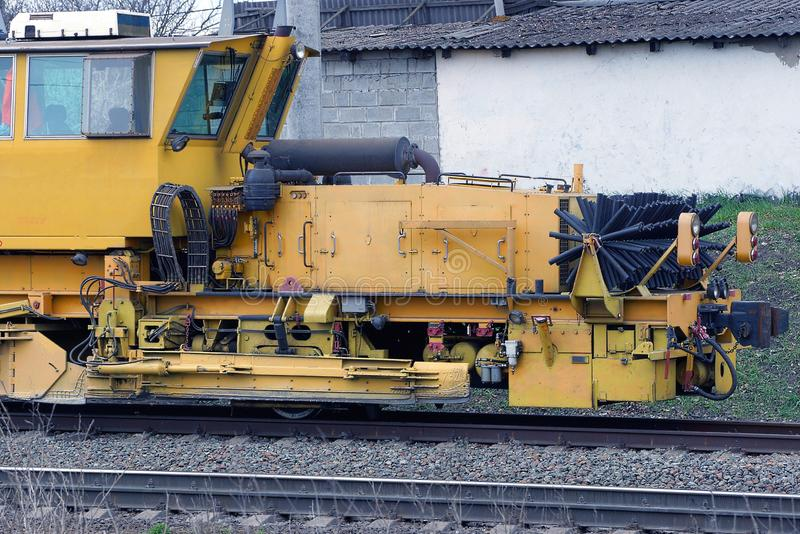 Yellow repair locomotive stands on the rails of the railway royalty free stock photo