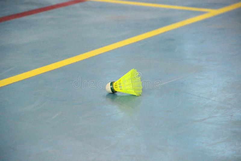 one yellow shuttlecock on the edge of the badminton court royalty free stock photos