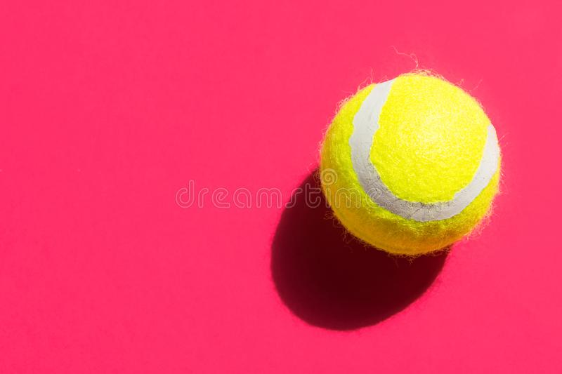 One yellow tennis ball on fuchsia pink background in bright sunlight sports active lifestyle competition victory concentration. Concept. Creative minimalist pop stock photos