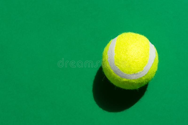 One yellow tennis ball laying on green court in bright sunlight sports active lifestyle competition victory concentration concept. Creative minimalist pop art royalty free stock photo