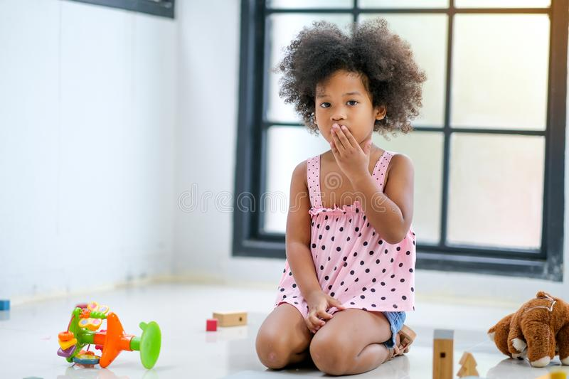 One young African girl sit and express of frighten or shock during plays some toys in the living room.  royalty free stock photos