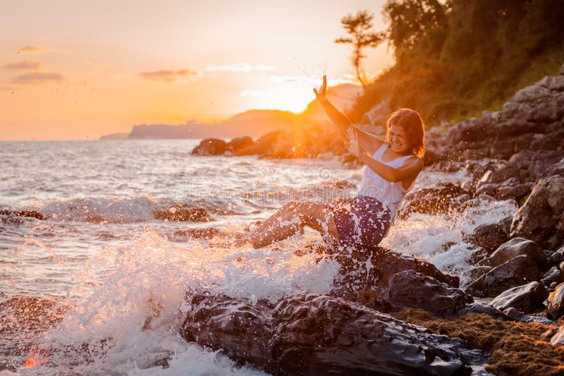 One young beautiful girl splashes and splashes the sea at sunset. Summer landscape sea, Islands and orange sunlight. The concept of freedom, euphoria, emotions royalty free stock images
