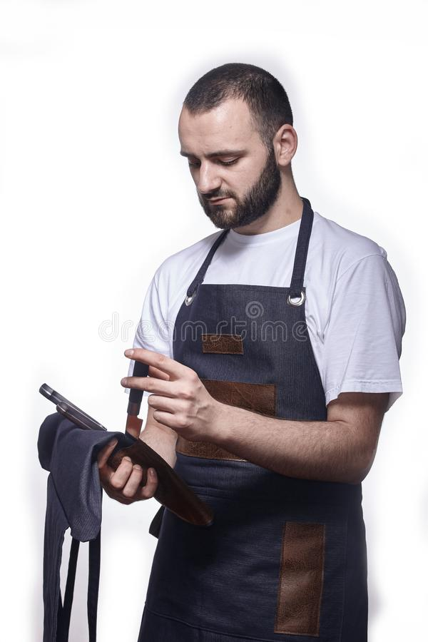 One young chef in uniform, holding set of knives. stock photos