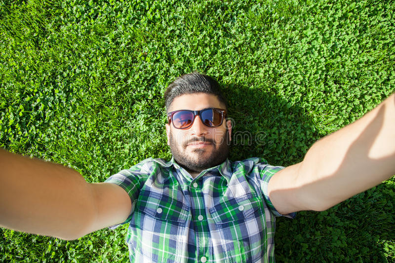 One young fashion middle eastern man with beard and fashion hair style is lying on a grass in a park taking selfie. stock images