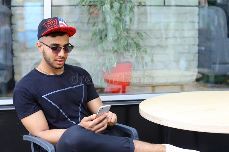 One young handsome arabian guy uses phone, sits chatting and sit stock photography