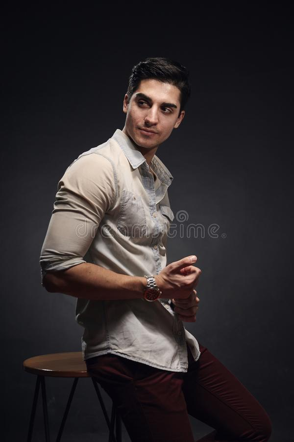 One young handsome man, handsome model, 20-29 years old, posing in studio, photo shoot. black background. casual clothes. wearing royalty free stock photo