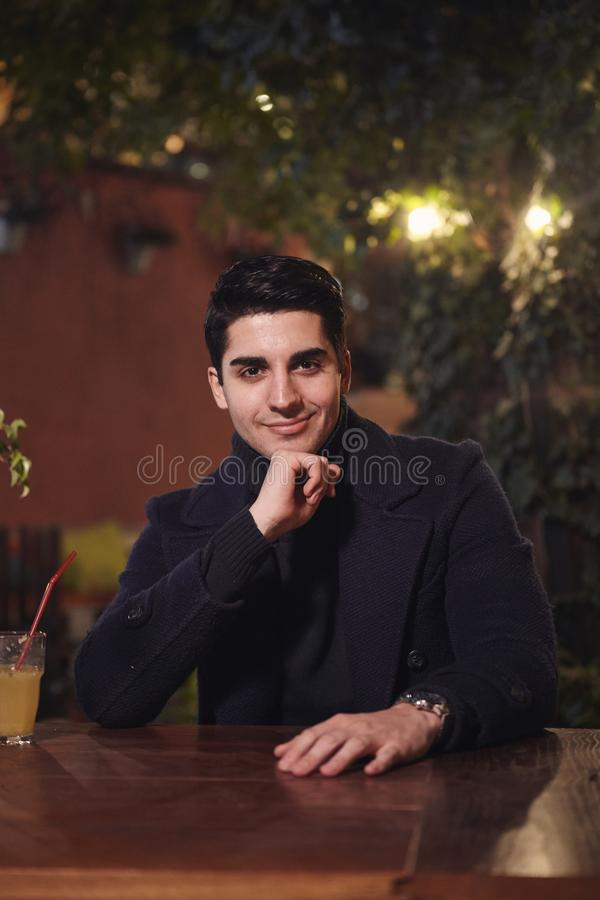 One young handsome man portrait, sitting in cafe garden at table, night outdoors, looking to camera. upper body shot stock photos