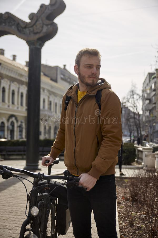One young handsome man, 20-29 years old, posing, standing and holding a bicycle, looking sideways. In a city.  royalty free stock photography