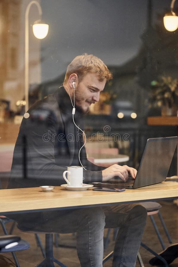 One young happy man, sitting in coffee shop and using his laptop, typing on keyboard, looking to computer screen. Shoot thought royalty free stock photography