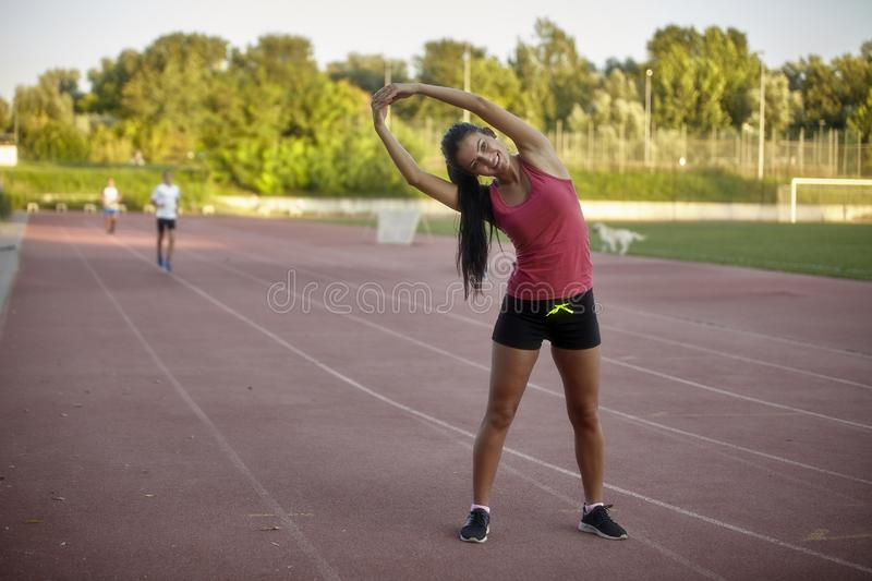 One young happy, smiling woman, stretching upper body - arms, leaning to one side. stock photos