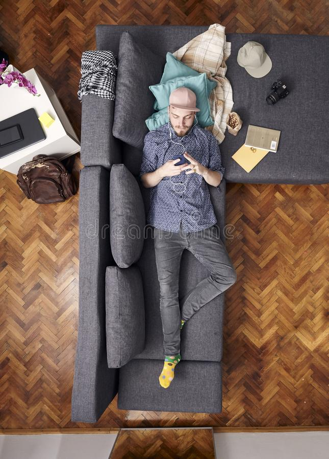 One young hipster, laying in couch in his room. using smartphone. bird`s eye view; view from above.  royalty free stock images