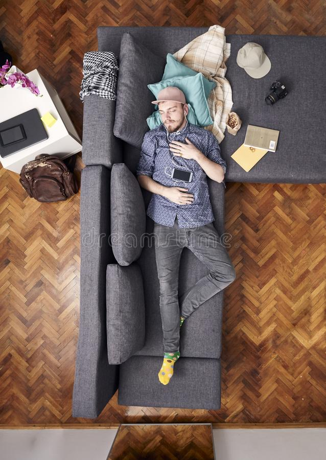 One young hipster man, laying in bed sleeping. whole sofa and bed visible, view from above.  royalty free stock photo