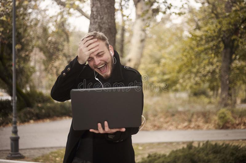 One young laughing man, can `t believe it, while he is candidly gesturing putting his palm on his forehead. Holding laptop in hand, communicating over Internet royalty free stock images