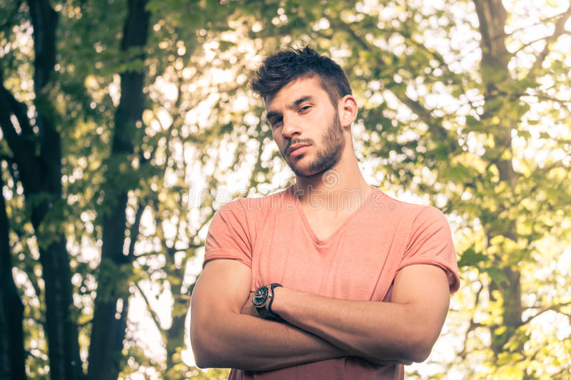 One young man, arms crossed, upper body,. Looking at the camera, outdoors sunny day, nature park royalty free stock image