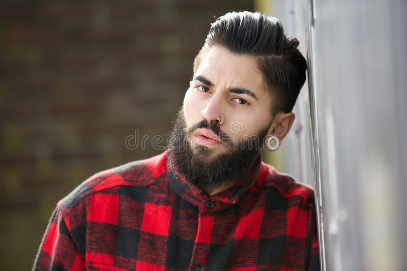 One young man with beard. Close up portrait of a one young man with beard and modern hairstyle standing outdoors royalty free stock photography