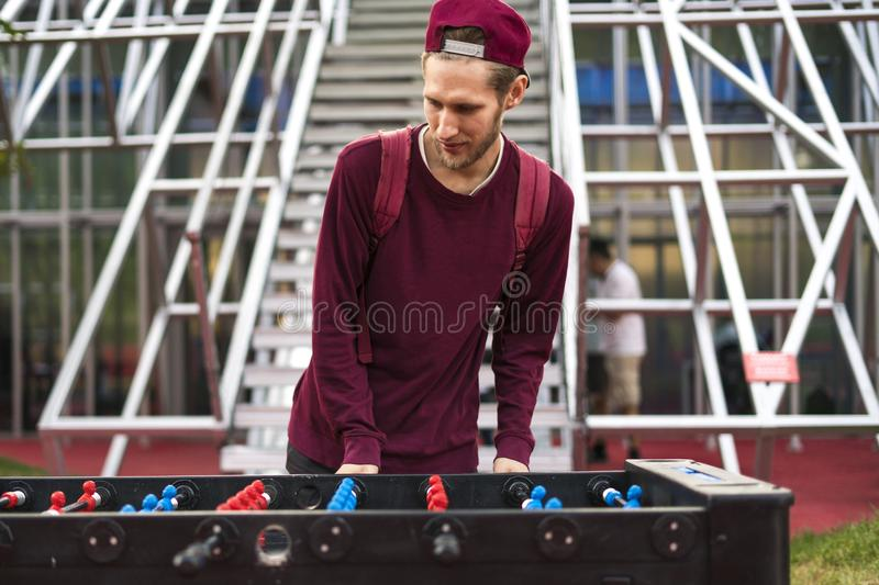 One young man in casual clothes playing foosball in the public park. table games concept. One young man in casual playing foosball in the public park. table stock photography
