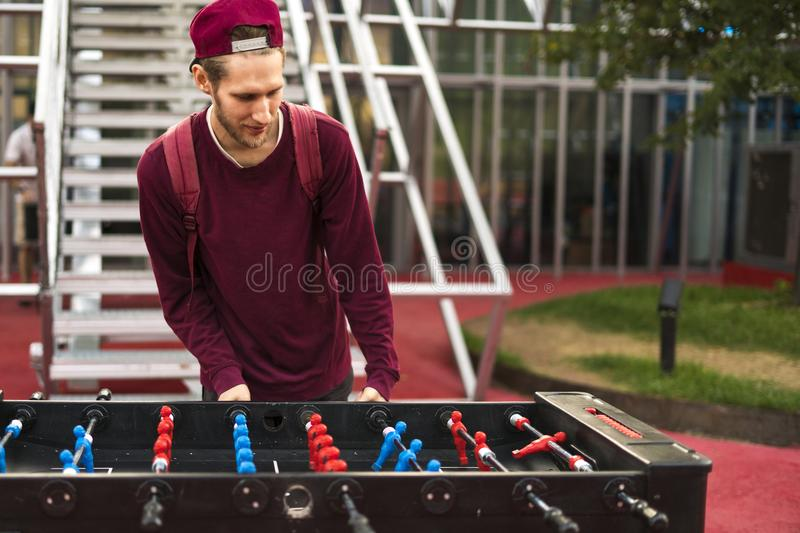 One young man in casual clothes playing foosball in the public park. table games concept. One young man in casual playing foosball in the public park. table stock images
