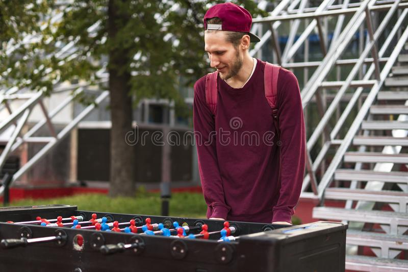 One young man in casual clothes playing foosball in the public park. table games concept. One young man in casual playing foosball in the public park. table royalty free stock photos