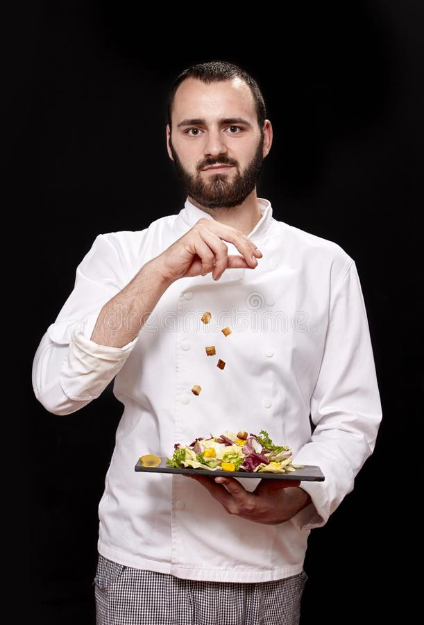 One young man, chief uniform, throwing croutons, holding fancy salad. stock images