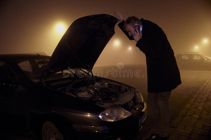 One young man, at dark night, looking at car engine, with car hood open. rural area.  royalty free stock photos