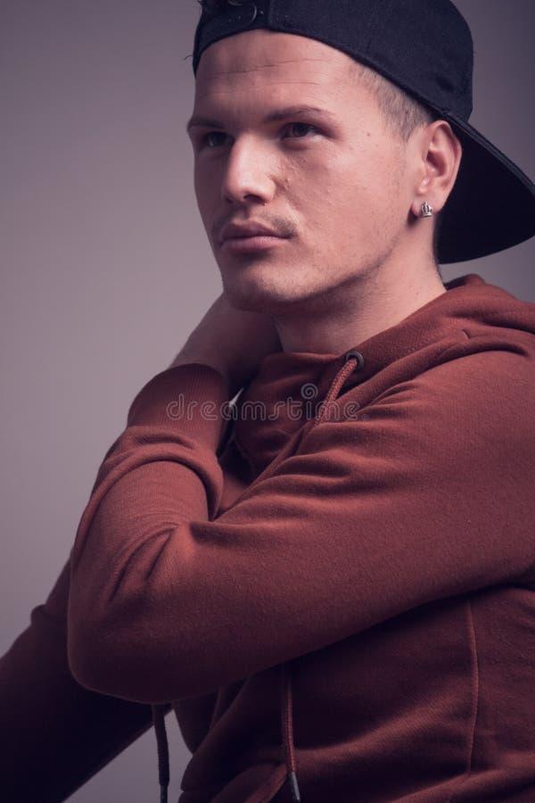 One young man, early 20s, boyish looks, posing in studio, casua. L clothes, sweatshirt cap, upper body shot, looking eways above stock photo