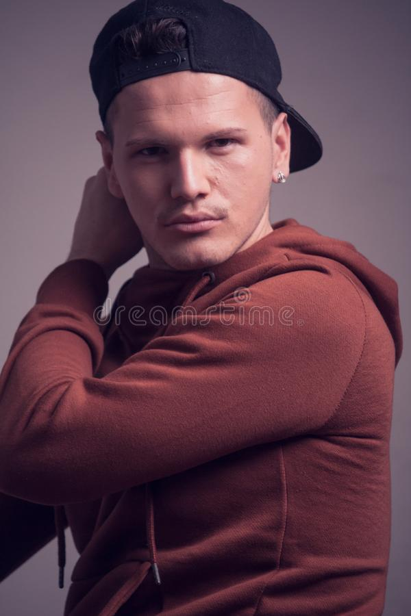 One young man, early 20s, boyish looks, posing in studio, casua. L clothes, sweatshirt cap, upper body shot portrait royalty free stock images