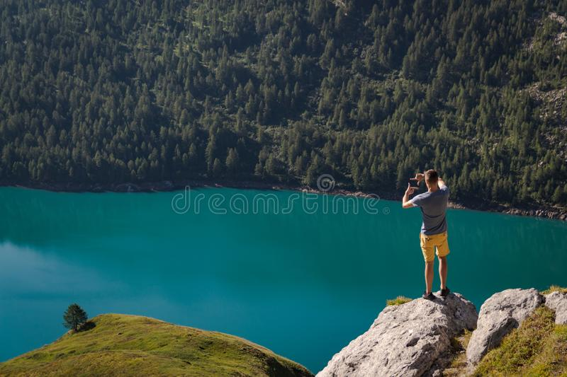 One young man framing a tree with his hands. lake ritom as background stock images