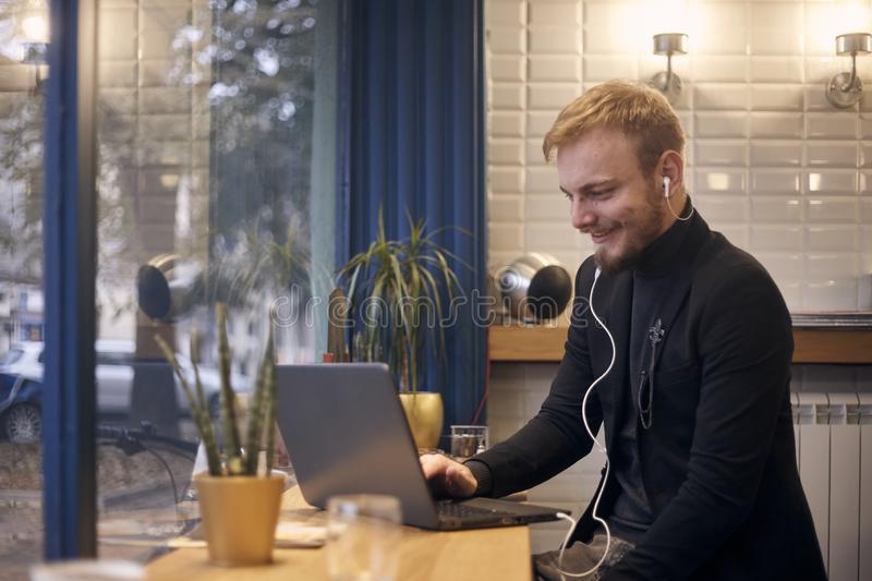One young man, sitting in coffee shop, drinking from cup working on laptop.  royalty free stock photo