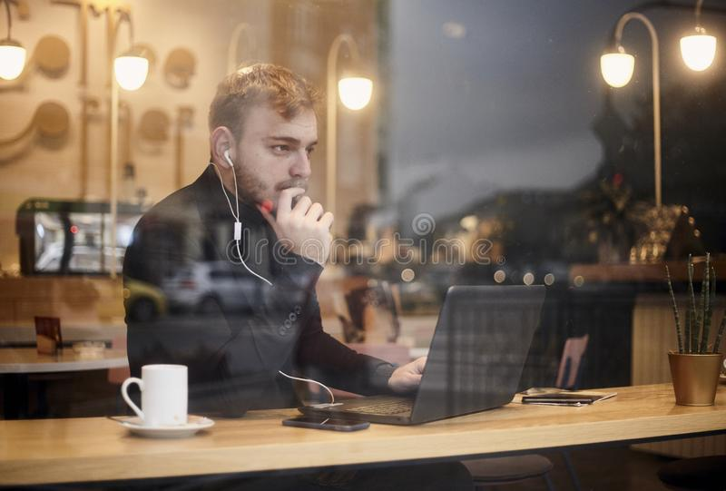 One young man, sitting in coffee shop and using his laptop while thinking and looking at street outside. Shoot thought window. Outside with reflections stock photo
