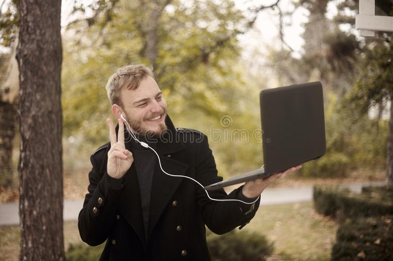 One young man, smiling and happy, holding laptop in one hand outside in park,. Communicating over Internet, video chat, could be with family of friend stock image