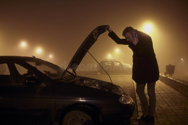 One young man, talking over phone, while holding car hood and looking at engine. It`s dark and nighttime, with mist and fog, rura. L area stock photos