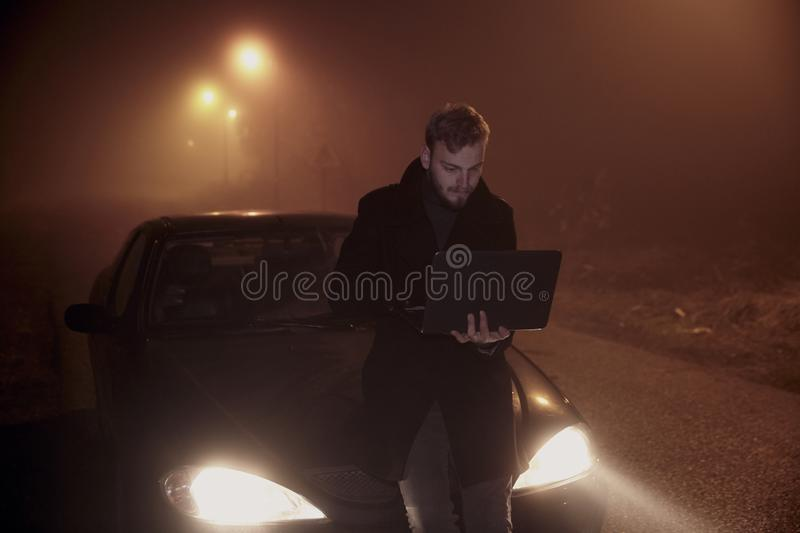 One young man using his laptop computer, on a car hood. It`s dark and night time, in rural area stock images