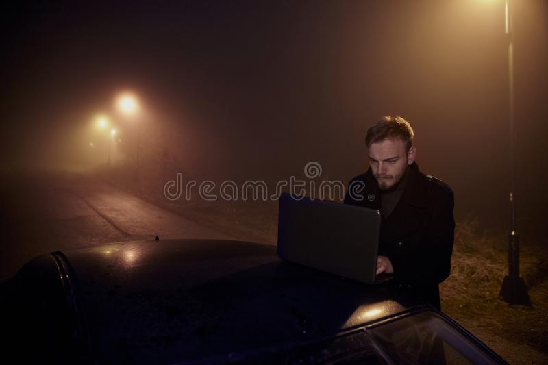 One young man, working using his laptop computer on a car roof, in dark night, rural area.  royalty free stock photography