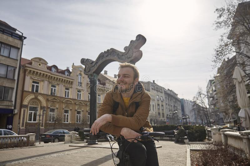One young man, 20-29 years old, relaxed enjoying sunny Autumn or Spring day, posing on his bicycle, looking sideways while smiling. In old European city square royalty free stock photo
