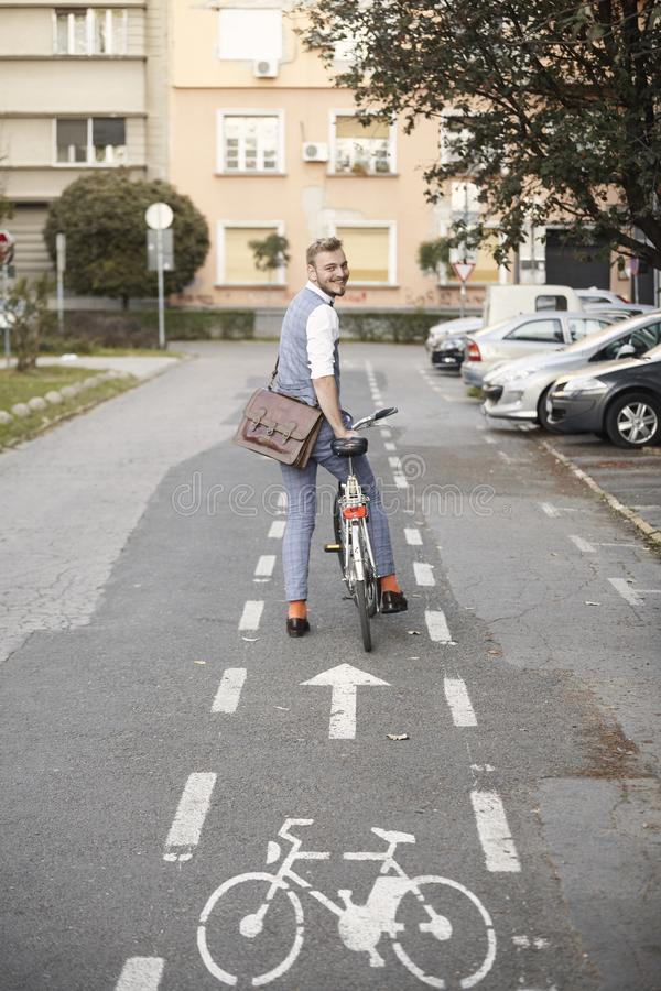 One young man, 20-29 years old, wearing hipster suit, smart casual, looking back to camera, rear view. in city on bike track royalty free stock image