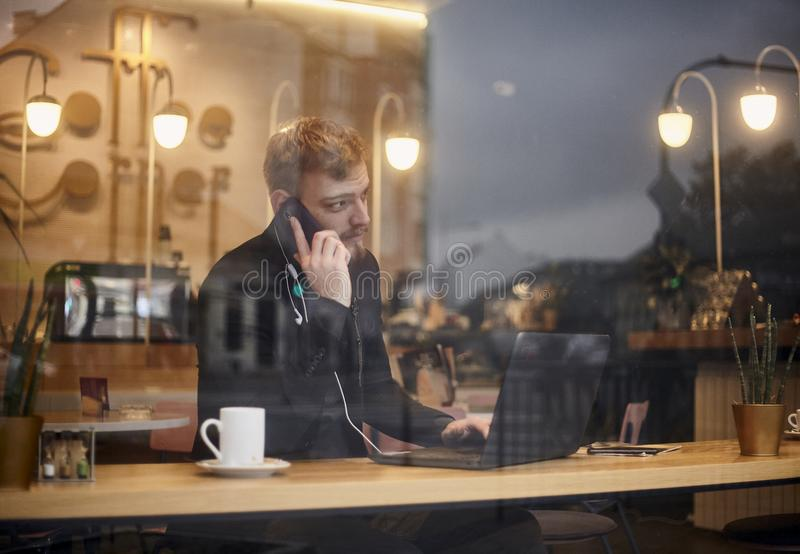 One young man, 20-29 years, sitting in coffee shop and using, his laptop while talking over phone. Shoot thought window outside. With reflections from outside stock image