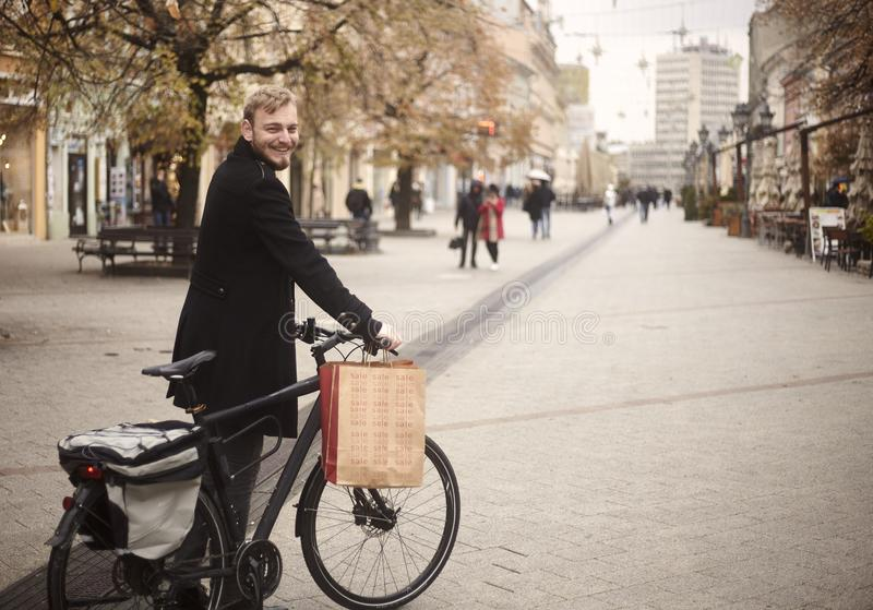 One young man, 20-29 years, standing in, pedestrian only, street holding his bicycle, and smiling to camera, with shopping bag. Pedestrians on street out of stock photos