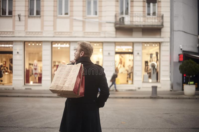One young mans back, rear view, 20-29 years old, handsome and stylish, standing on a pedestrian street in city, looking,. While holding two shopping bags on his royalty free stock photos
