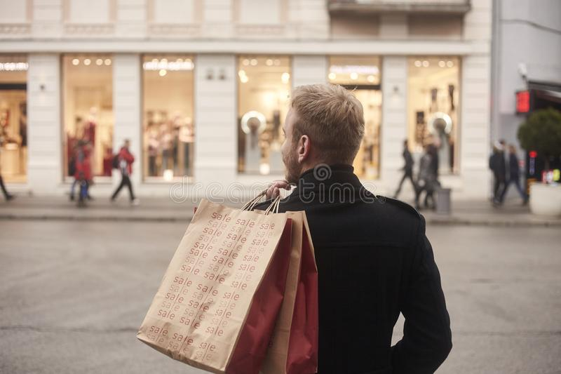 One young mans back, rear view, 20-29 years old, standing on a pedestrian street in city,. Looking, while holding two shopping bags on his back. Store front stock photography