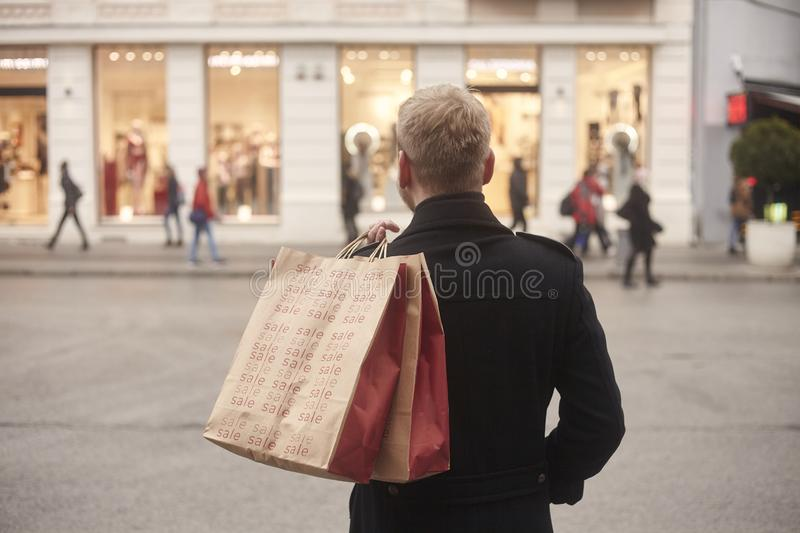 One young mans back, rear view, 20-29 years old, standing on a pedestrian street in city, looking, while holding two shopping bags. On his back. Store front stock photos