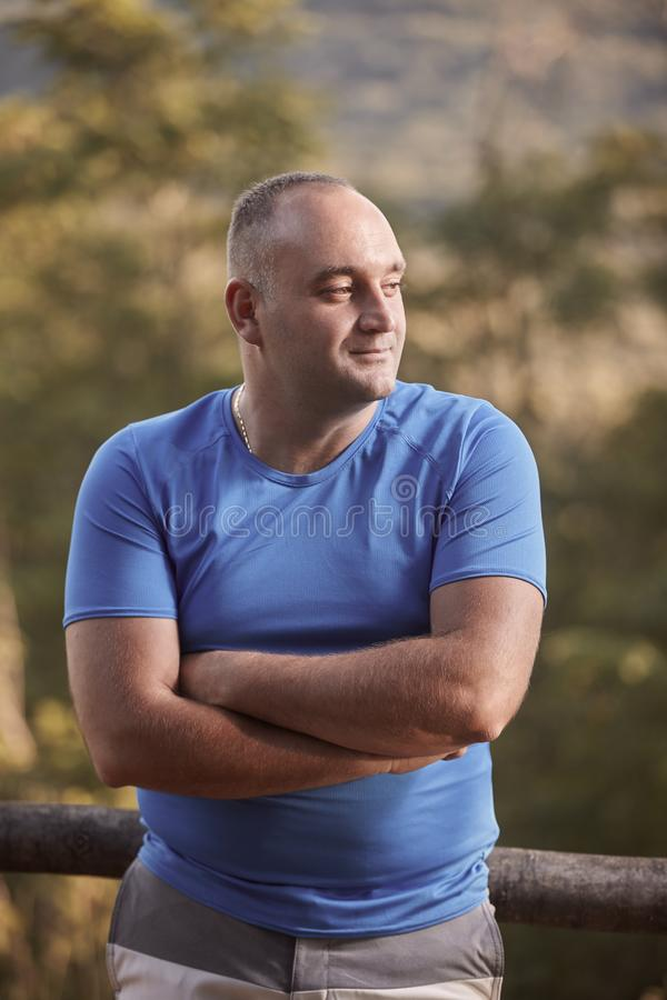 One young overweight man, 30-35 years, looking sideways, arms crossed, outdoors portrait, upper body shot stock photo