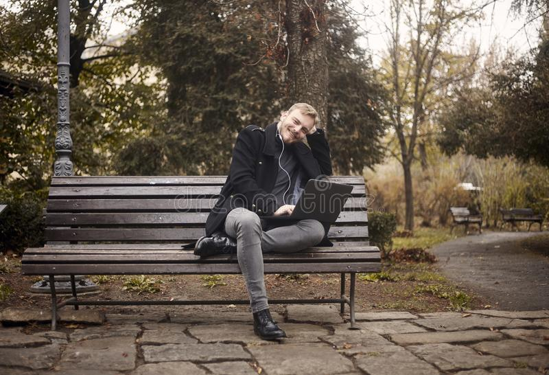 One young relaxed man, sitting on bench in public park, using laptop, stock photos