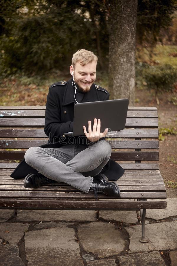 One young relaxed and smiling man, sitting casually on bench with crossed legs in public park,. Using laptop holding it with one hand. Formal wear or smart stock images