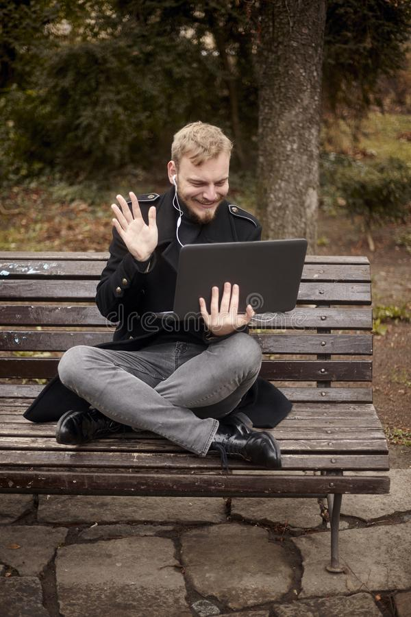 One young relaxed and smiling man, sitting casually on bench with crossed legs in public park, using laptop with video call. Or video chat, waving hand `Hello royalty free stock photo