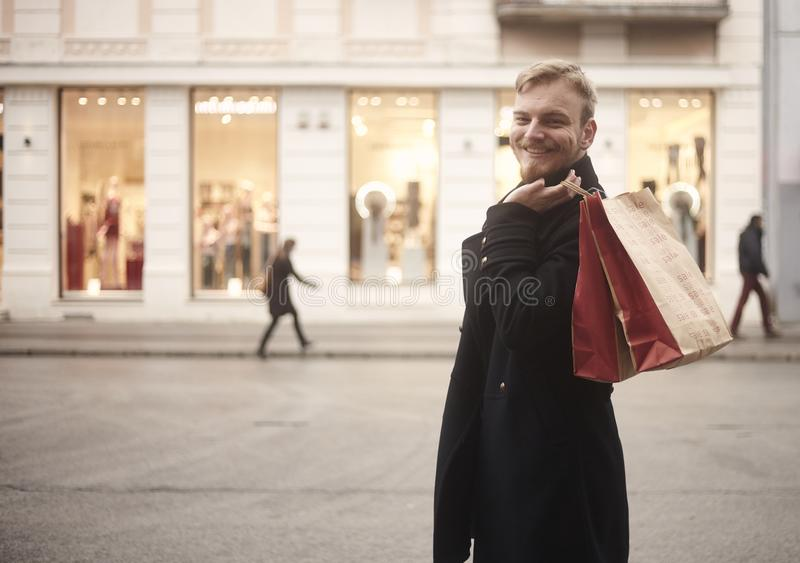 One young smiling and happy man, 20-29 years old, handsome and stylish, looking to camera while holding two shopping bags on his. Back. Pedestrians walking in stock photos