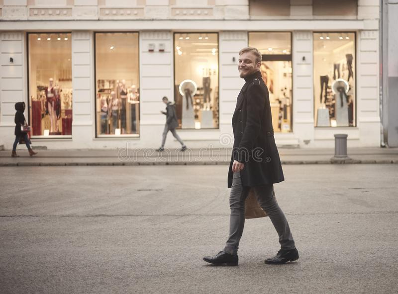 One young smiling and happy man, 20-29 years old, handsome and stylish, walking in city street with no cars, pedestrians walking. In background with store stock photo