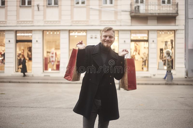 One young smiling and happy man, 20-29 years old, on a pedestrian street, looking to camera, while holding two shopping bags with. Arms outstretched. Store royalty free stock photography